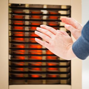 Warming hands by a heater