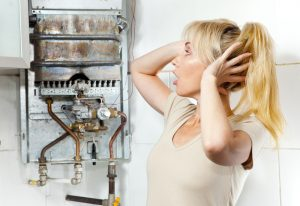 Woman looking stressed at a broken water heater