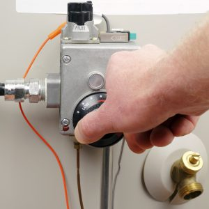 man changing water heater temperature